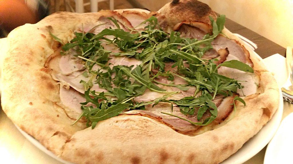 Pizza bianca met prosciutto en rucola